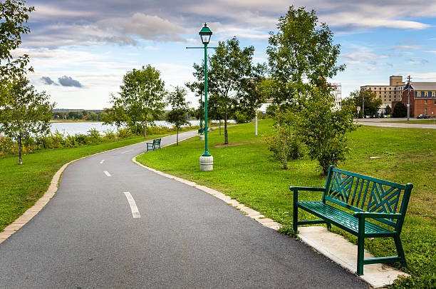 riverside paved path and cloudy sky - fahrradwege stock-fotos und bilder