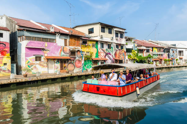 Malacca, Malaysia - April 21, 2019:  Riverside scenery of a cruise crossing by the Malacca River. It has been listed as UNESCO World Heritage Site since 7/7/2008. stock photo