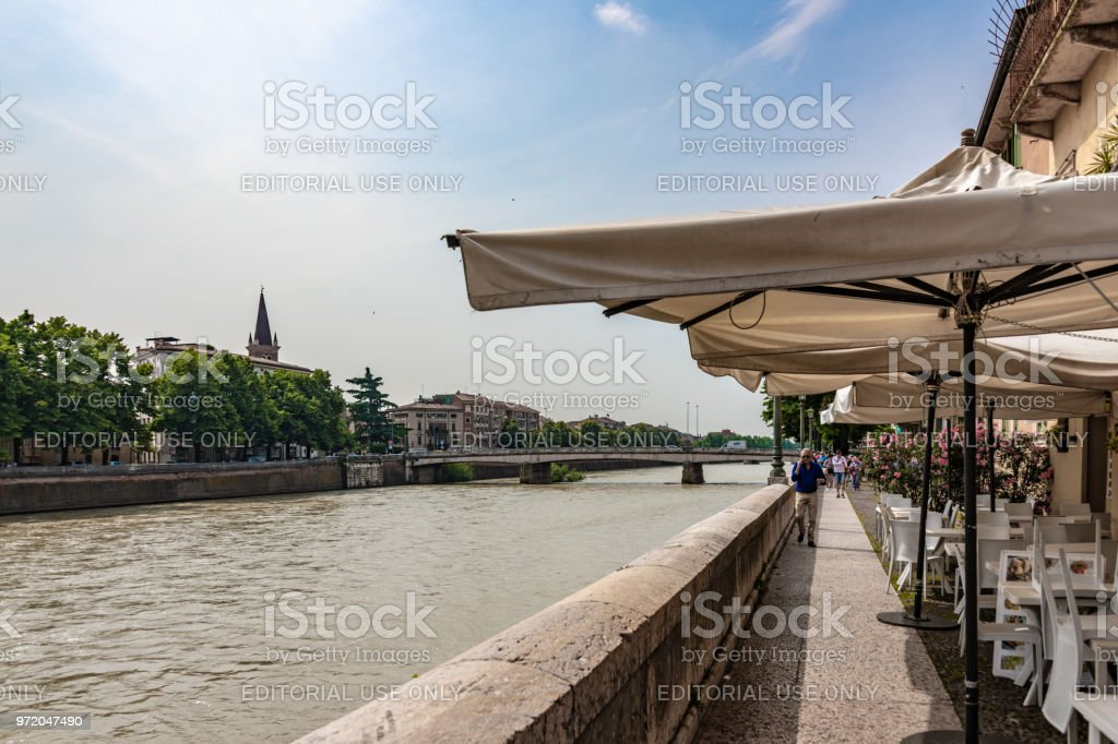 Riverside walk with a cafe in Verona, Italy stock photo