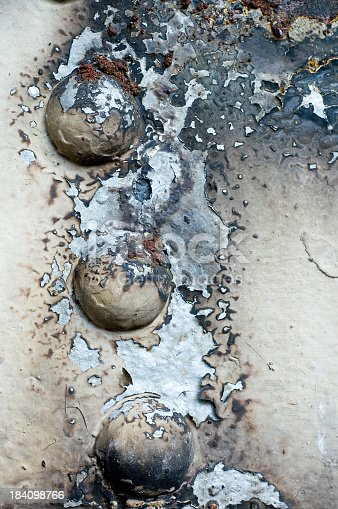 Rust and corrosion on a riveted surface.
