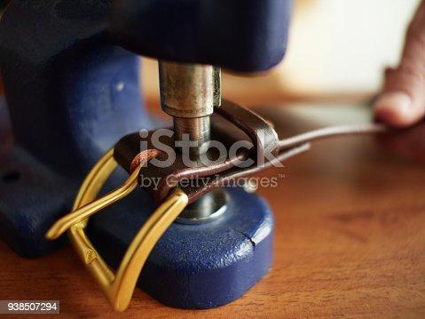 istock Riveting the brass belt buckle. 938507294