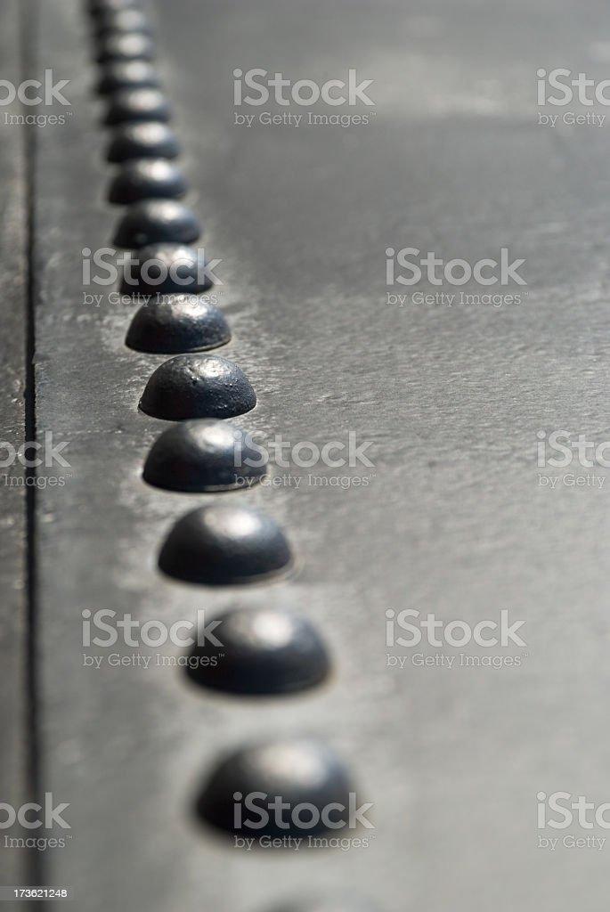 Rivets in row (shallow DOF) royalty-free stock photo