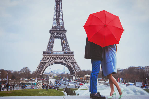 Rmantic couple in Paris kissing near Eiffel towe. romantic holidays for couple in Paris, honeymoon vacation in France, Europe, man and woman kissing near Eiffel tower romantic activity stock pictures, royalty-free photos & images