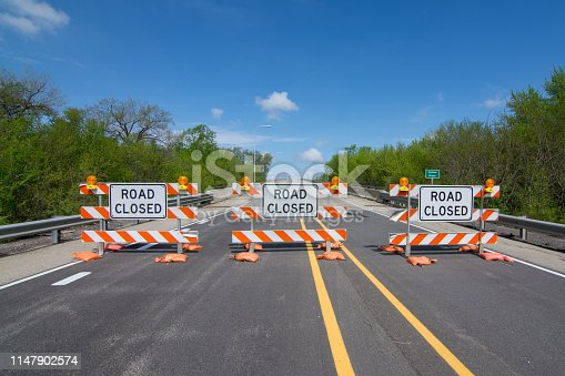 Road closed signs on a bridge over the swollen Illinois river after flooding on the roadway.