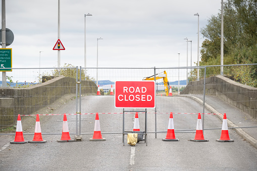 Road ahead closed sign with traffic cones and red barrier fence crossing UK
