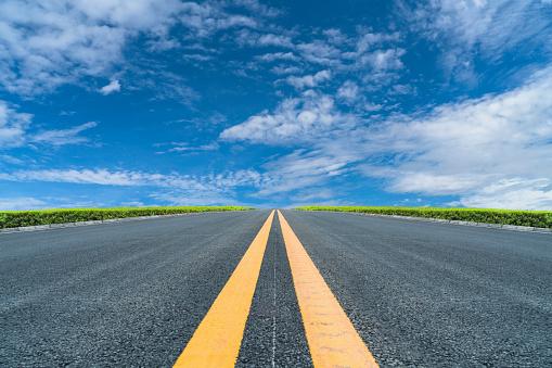 empty asphalt road to horizon under cloudy sky.