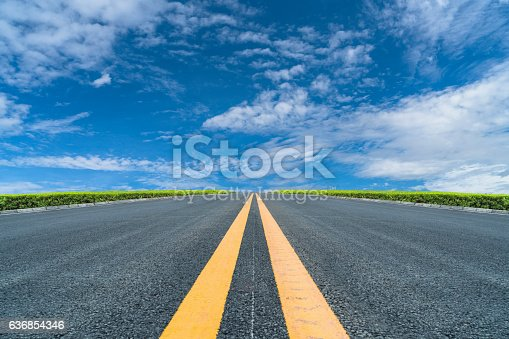 empty asphalt road to horizon under cloudy sky.