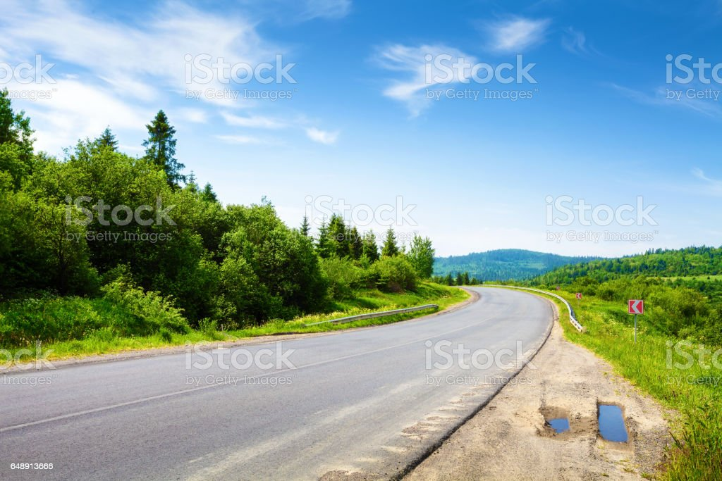 Road along mountain forest in summer day stock photo