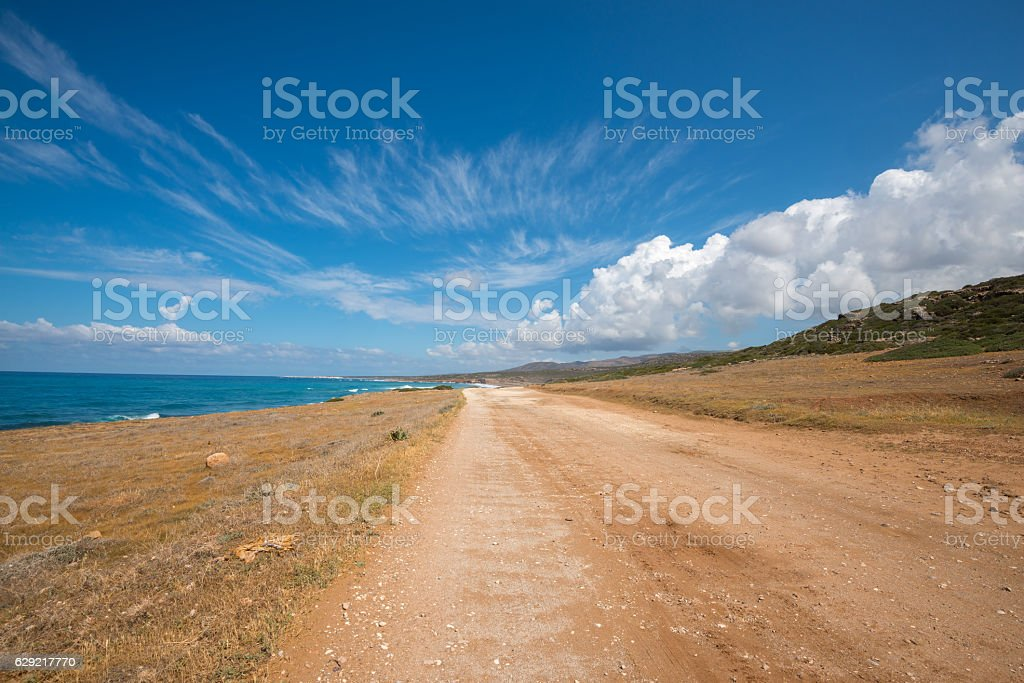 Road along the coast stretches to the clouds stock photo