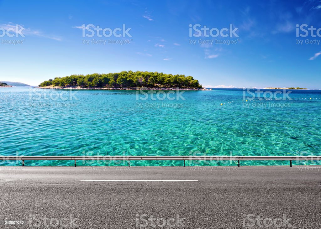 Road and clean sea water with island on horizon stock photo