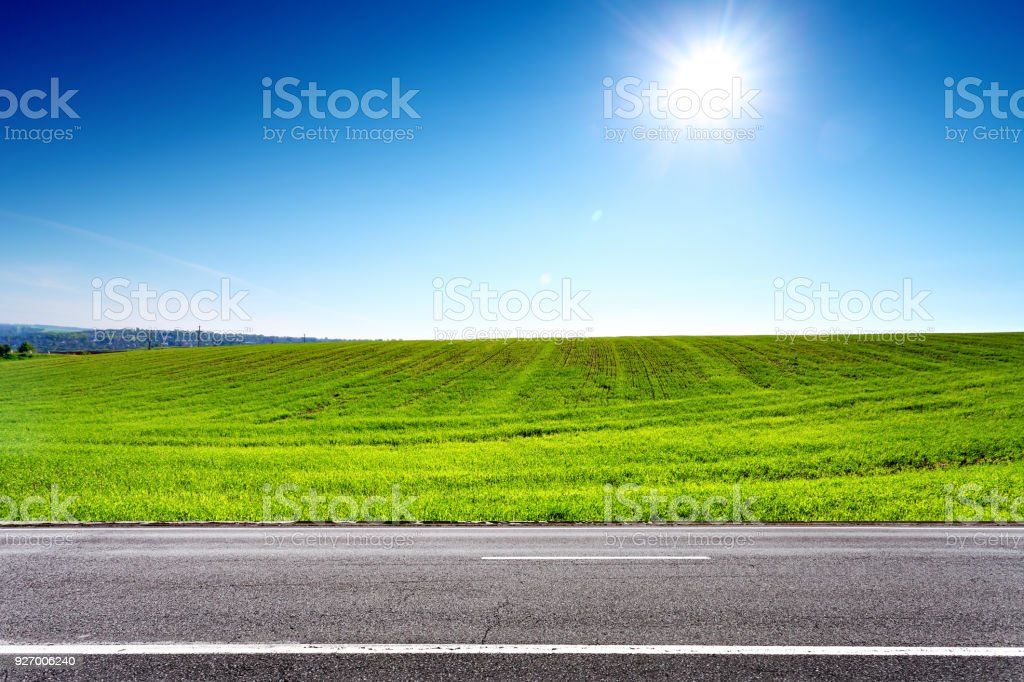 Road and green spring field with sun on blue sky stock photo