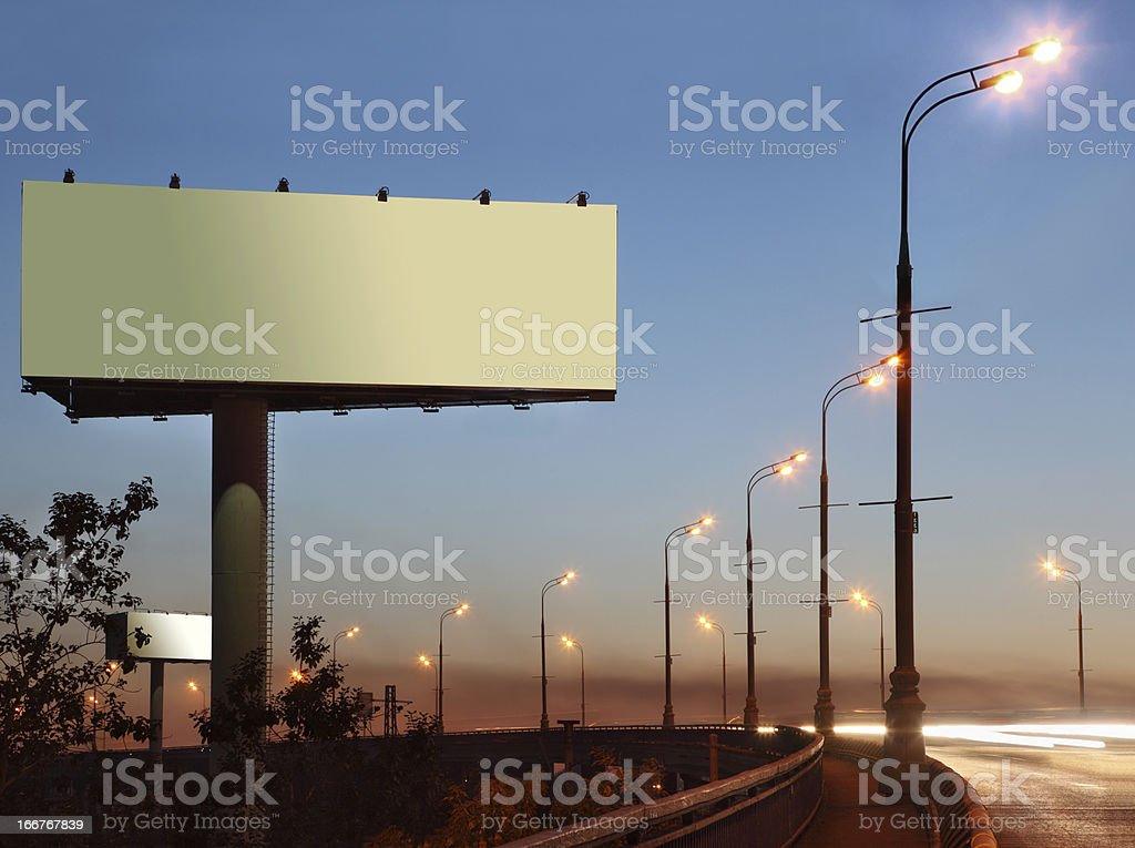 Road and large blank billboard at evening royalty-free stock photo