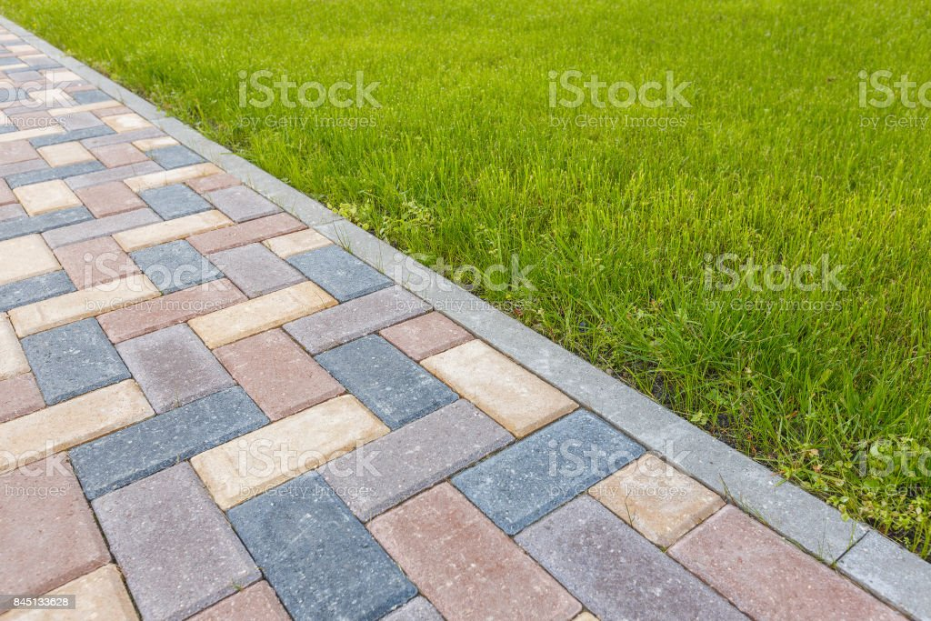 road and lawn divided by a concrete curb stock photo
