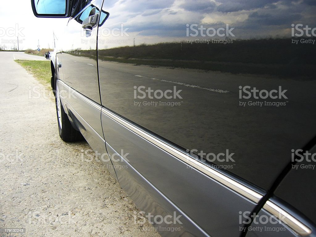 Road and moody sky reflection in car doors royalty-free stock photo
