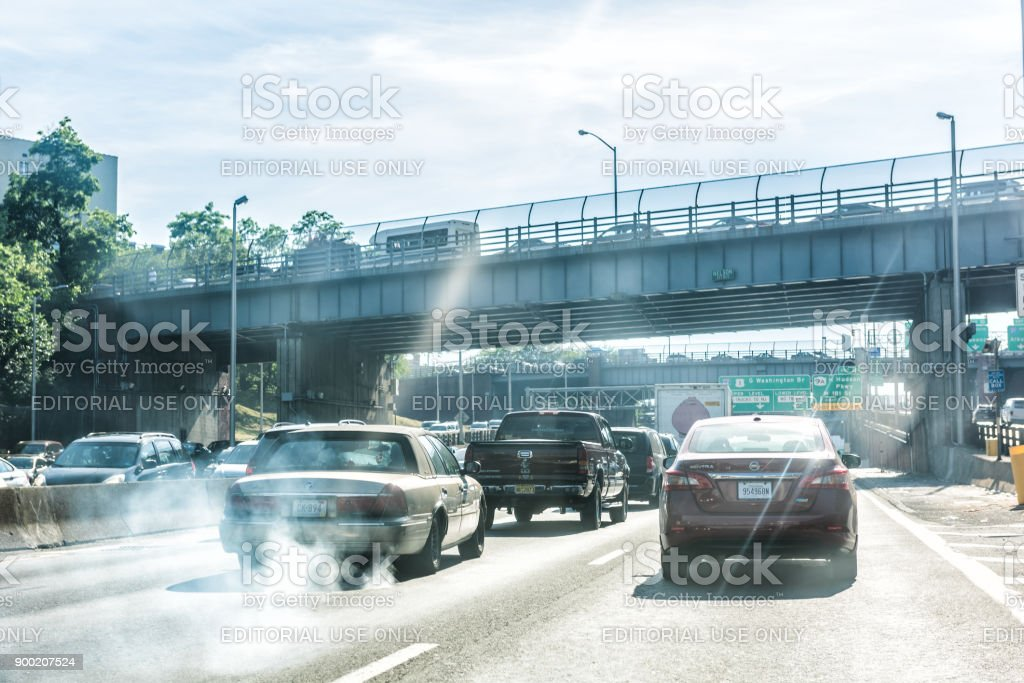 Road and street highway in NYC with sign for George Washington Bridge, smoke coming out of exhaust pipe of car stock photo