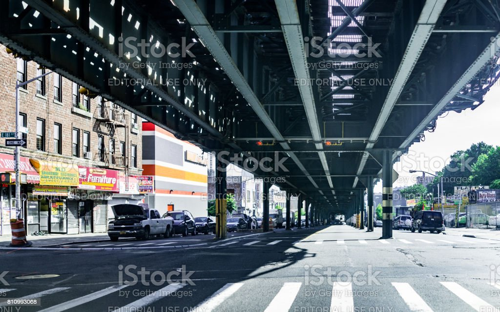 Road and street under subway railroad with restaurants and shops with sidewalk in downtown Fordham area stock photo
