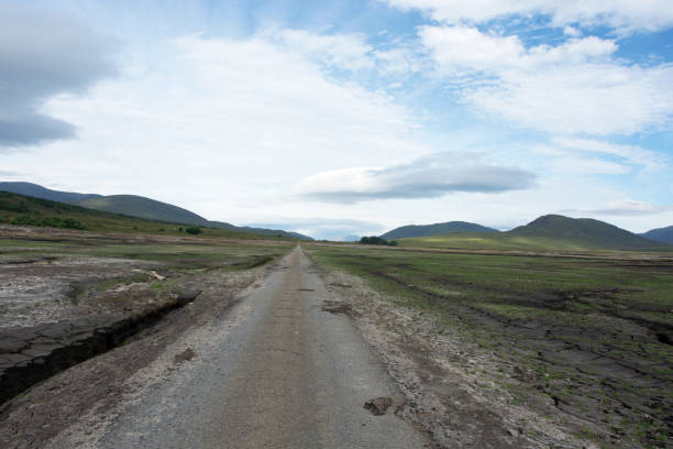 Road and surrounding loch bottom which has been revealed due to low water levels in Loch Glascarnoch stock photo