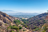 Southern California mountain and foothill hiking trails in morning summer sun with cities of inland empire in the distance