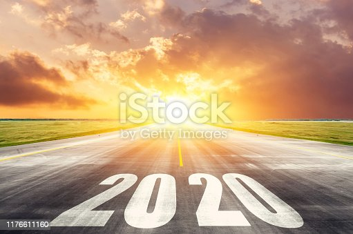 Road asphalt road with the inscription 2020 year with the rising sun in the morning. The concept of the beginning of new goals and affairs