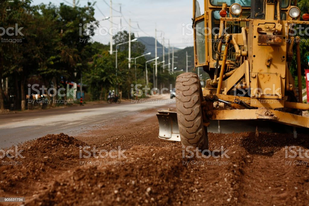 road being resurfaced and graded, widened and smoothed out by heavy machinary stock photo