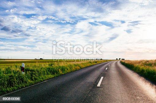 Empty road between green fields in Germany