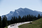 A large group of men compete in a road bicycle race on a sunny day in the Rocky Mountains of Canada.