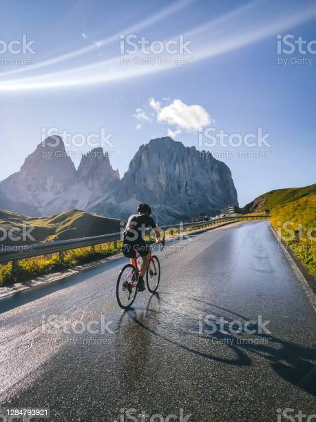 Photo of Road bicyclist rides up a road in the mountains