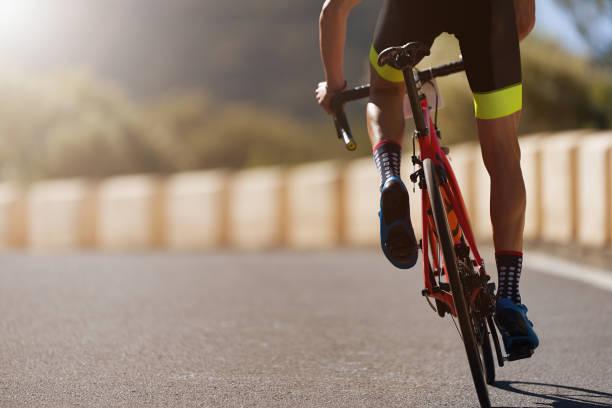 ciclista su strada uomo ciclismo - ciclismo foto e immagini stock