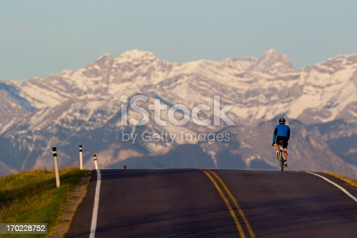 A male road bicyclist rides west towards the Rocky Mountains in Alberta, Canada.