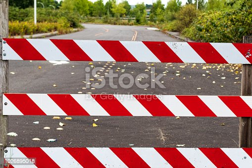 Road block barricade sign stripes white and red with road behind