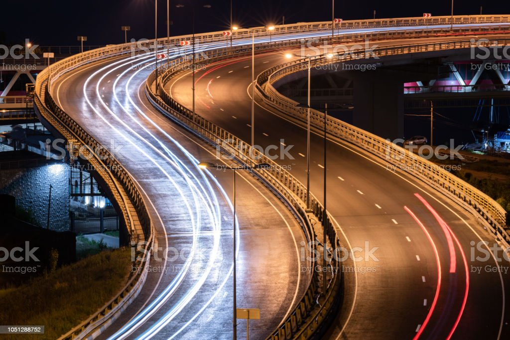 Interchange bridge road with car light streaks. Night light painting...