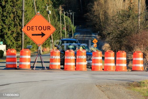 A horizontal image of a road barricaded with traffic control barrels and a detour sign.