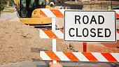 Road closed sign displayed in the middle of the street during road construction. A tractor and pile of dirt are behind the sign.