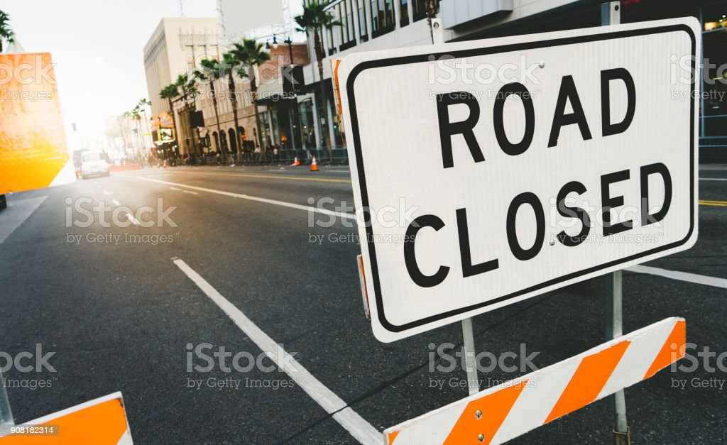 Road closed sign and traffic cone in the street. Traffic control sign road closed in the city. stock photo