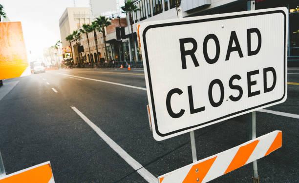 road closed sign and traffic cone in the street. traffic control sign road closed in the city. - queue foto e immagini stock