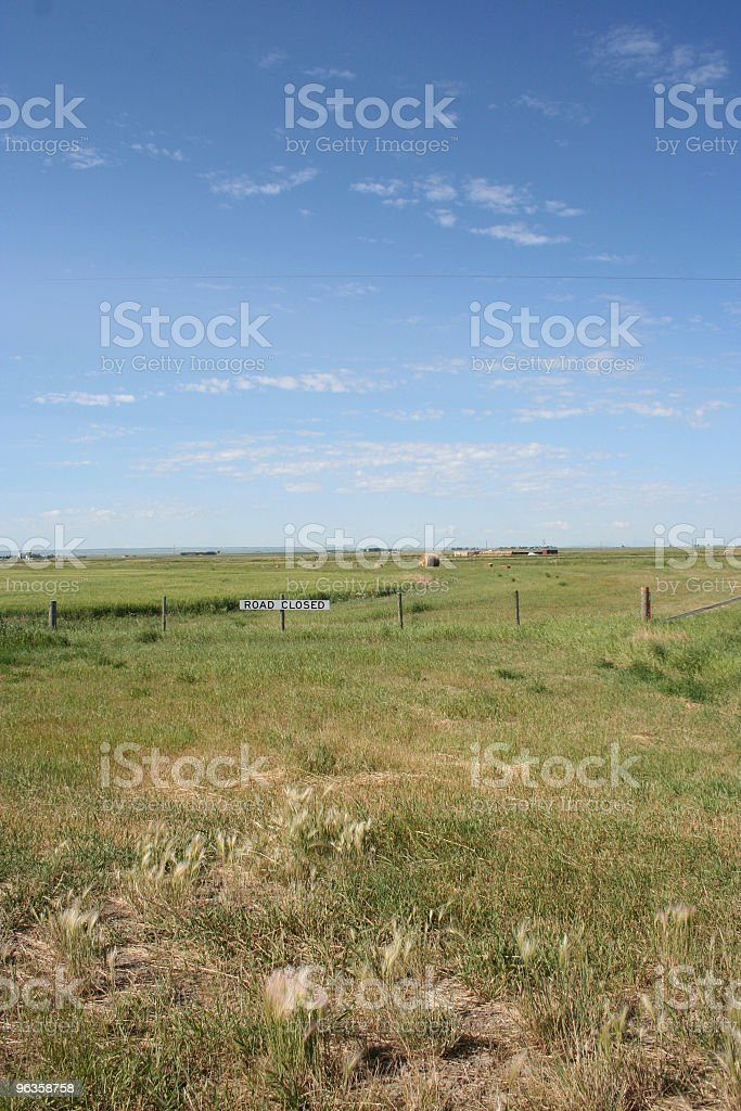 road closed sign hangs on fence in a field royalty-free stock photo
