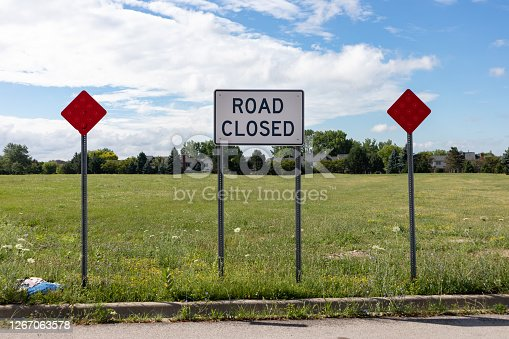 A road closed sign on a dead end street in front of a flat green field during summer in suburban Bolingbrook Illinois