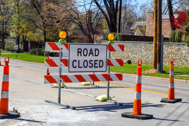 road closed sign in the middle of four lane highway in residential neighborhood in early spring - barricata foto e immagini stock