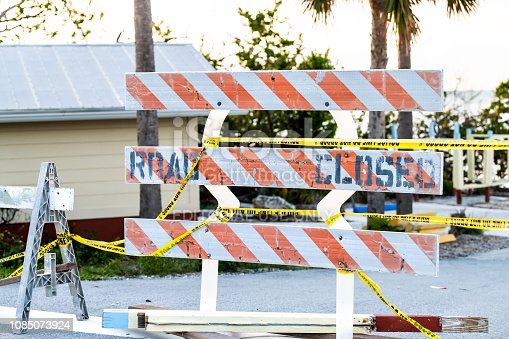 Islamorada, USA - May 1, 2018: Road closed wooden orange sign, stand, standing by coast, shore in Florida after destruction of hurricane Irma with nobody, yellow tape with palm trees, ocean, sea