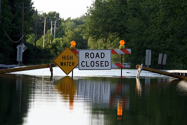 a road closure signage as water covers the road - natural disaster stock pictures, royalty-free photos & images