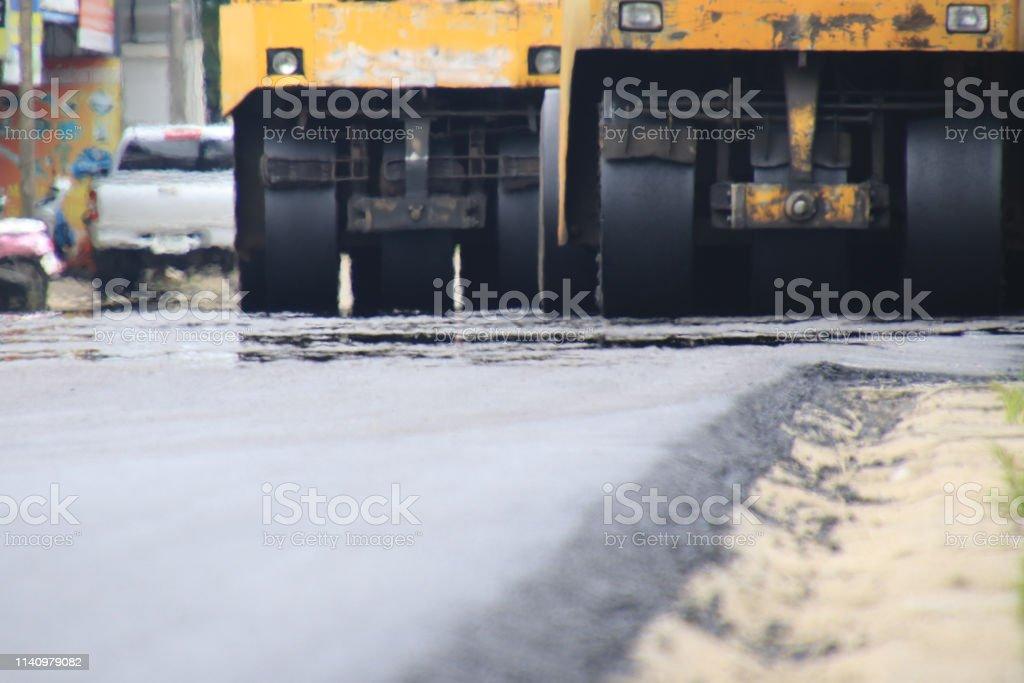 Road construction asphalt road by worker and roller machine. Asphalt...