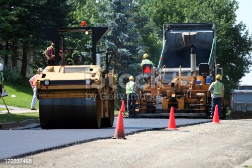 An asphalt spreader is used to place the first layer of asphalt on a city street renewal project.