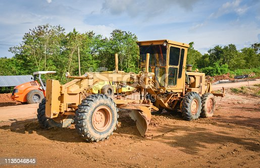 Road construction with motor grader / yellow of modern grader with wheel tractor working on construction site