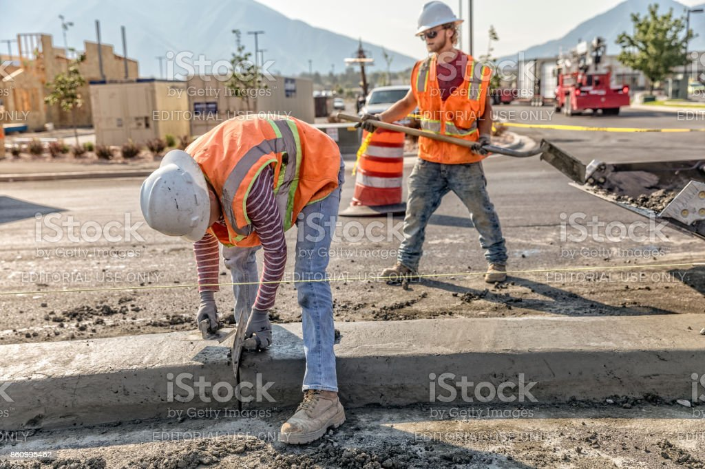 Road construction worker cleans off concrete from a center medium that was just laid in Spanish Fork, Utah stock photo