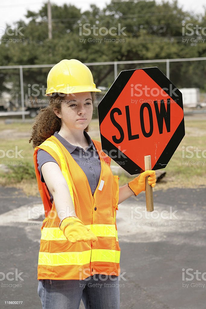A female construction road crew member holding a slow sign for...