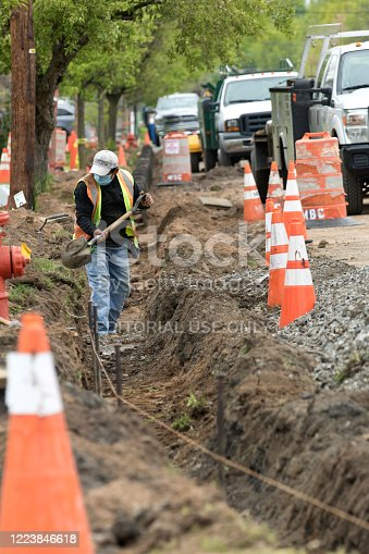 Saddle Brook, New Jersey, USA - May 8, 2020: Worker preparing trench for the installation of forms for concrete during road curb construction.