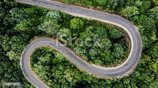 Winding road seen from above, with two hairpin bends, surrounded by a green forest with lush foliage. Aerial view, no people.