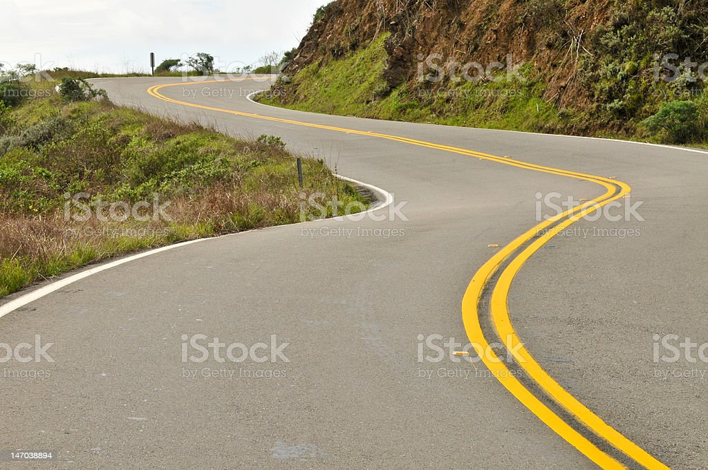 Road curves up a hill stock photo