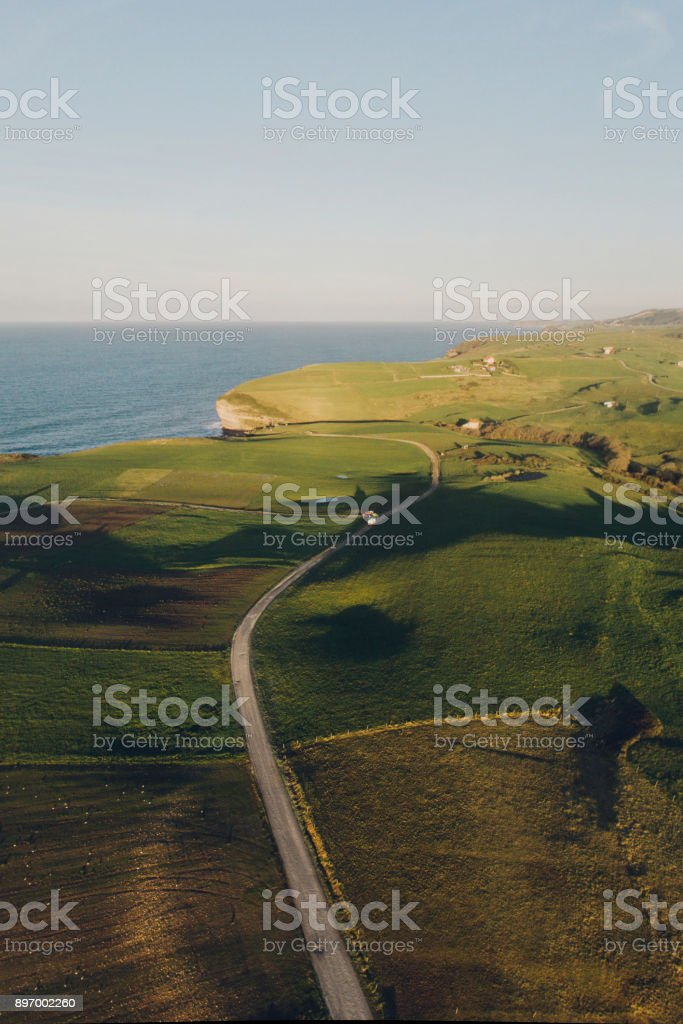 A road in a beautiful green landscape as seen from above.