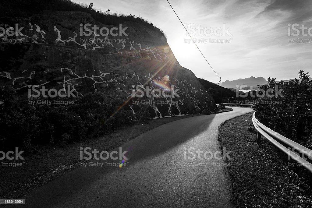 Road going through mountains towards the setting sun royalty-free stock photo